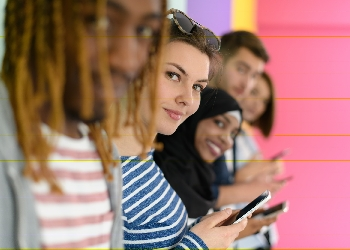Diverse group of teenagers use mobile devices while posing for a studio photo