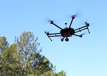 Photo of a drone flying through the air with sky and trees in the background.