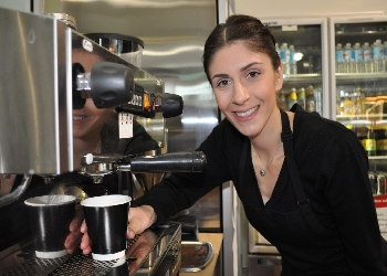 Photo of a young woman smiling next to the coffee machine at the Shedley Theatre Cafe.